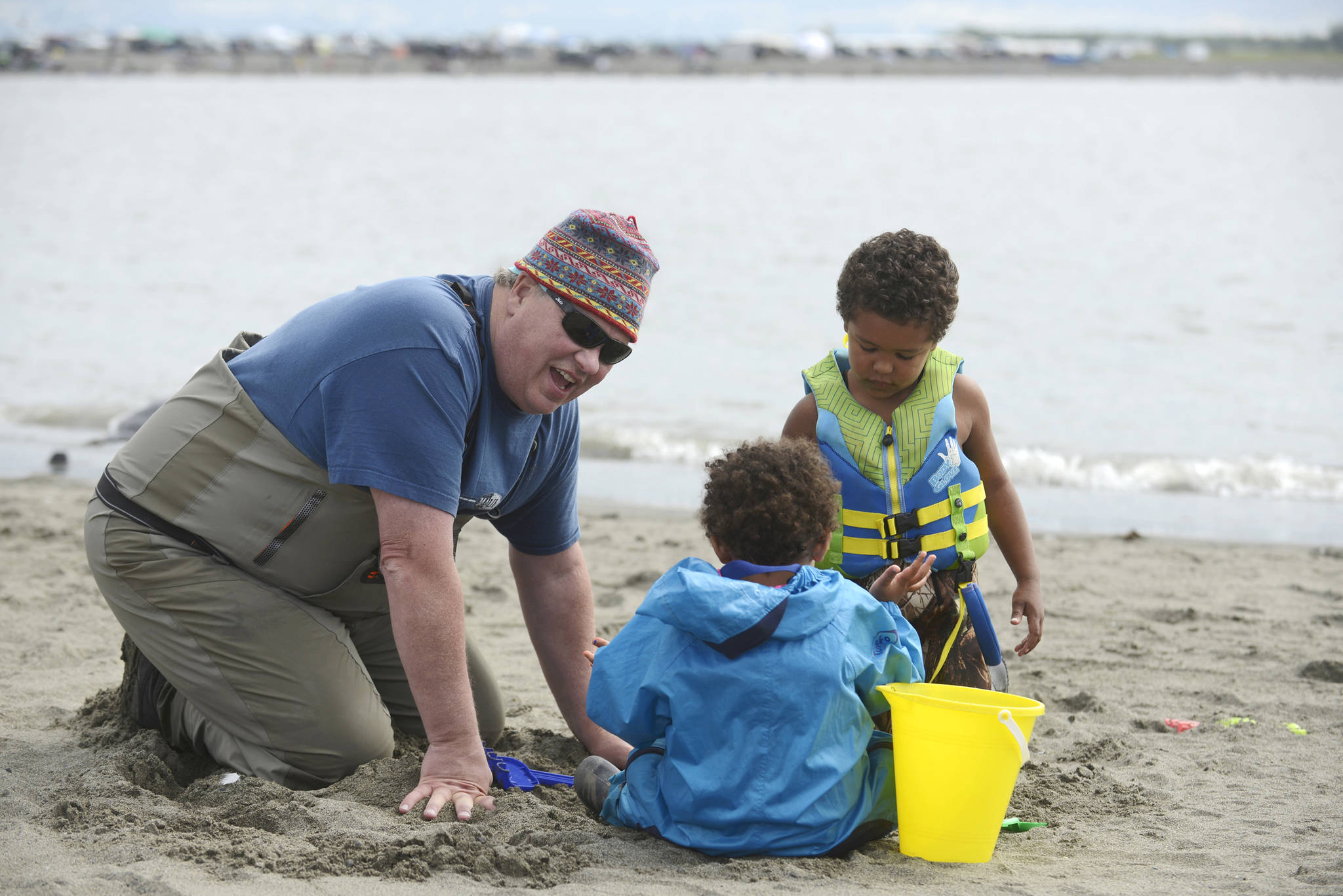"Dipnetter Brad Gamblin (left) digs in the sand of Kenai's north beach with his grandchildren Stella (in blue) and Marly Wilson on Thursday, July 26, 2018 in Kenai, Alaska. The three, plus grandmother Cher Gamblin, brought the grandchildren on their first dipnetting trip this year. The morning, Brad Gamblin said, ""was very productive."" Getting up early, he said the family had caught a dozen salmon by 9 a.m. (Ben Boettger/Peninsula Clarion)"