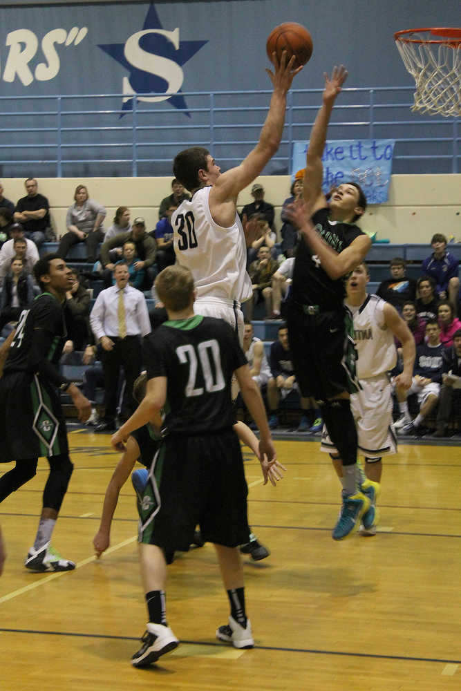 Soldotna's Daniel McElroy attempts a floater over Colony's Damien Fulp, Saturday at Soldotna High School. The Stars lost 65-43.