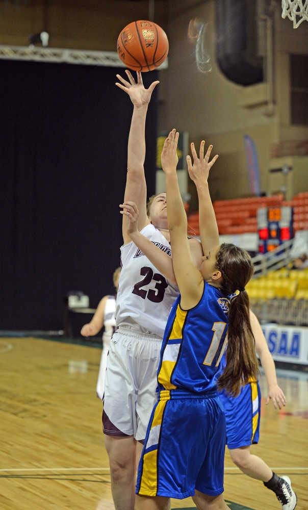 Nikolaevsk's Nianiella Dorvall (32) scores over Cook Inlet Academy's Nicole Moffis (11) during the 1A girls third-place game at the 2014 high school state basketball championships at Anchorage's Sullivan Arena on Wednesday.