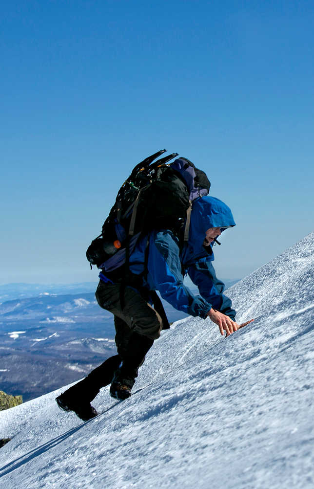 "In this Friday, April 4, 2014 photo, Joe Murdzek scrambles up a snowfield while climbing Mount Adams in the Northern Presidential Range of the White Mountains in New Hampshire. Murdzek, 47, of East Hartford, Conn, and three high school friends have made a tradition of getting away on overnight climbing trips as a way to ""hit the reset button"" from the daily grind. (AP Photo/Robert F. Bukaty)"