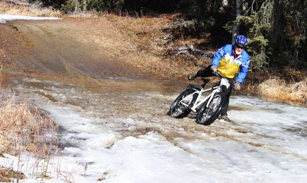 """Photo by Kelly Sullivan/ Peninsula Clarion Many cyclists had to get off and walk their """"weapons"""" through the muddy pools of melting ice on Wolverine trail, Saturday, April 19, at the Tsalteshi Trail."""