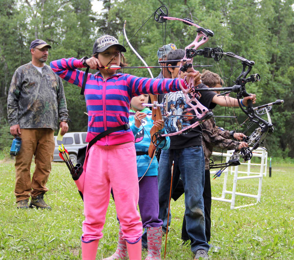 Photo by Dan Balmer/Peninsula Clarion Kira (front) and Lena Cook from Palmer try to be the first to hit an apple with their arrow during an archery shooting tournament at the Kenai Peninsula Archery Range Sunday in Soldotna. Kira placed second in the feamle cubs freestyle division.