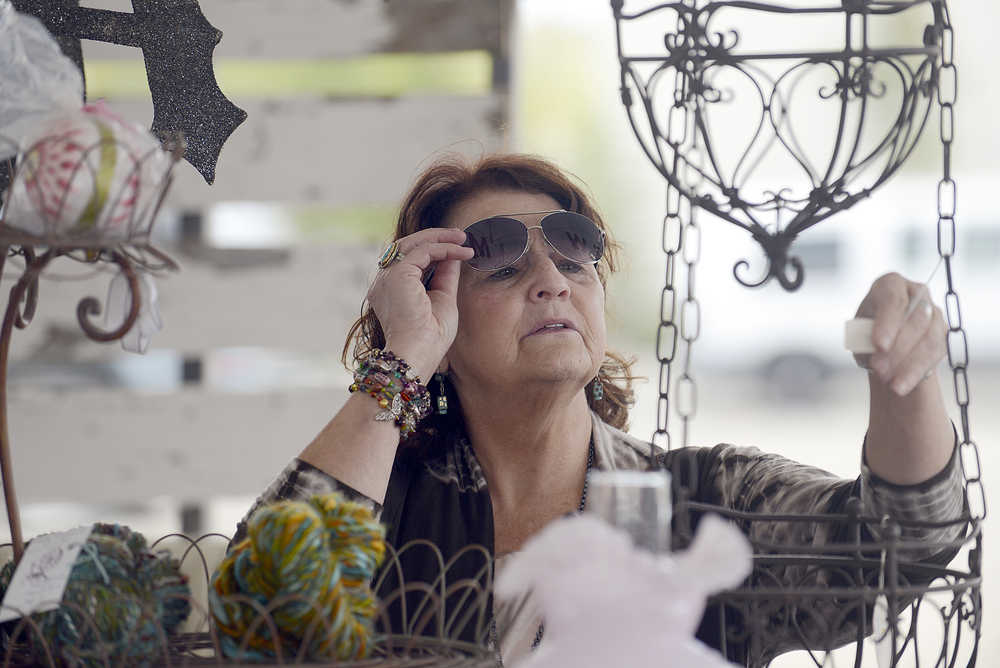 Photo by Rashah McChesney/Peninsula Clarion  Margo Bouchard checks the price of a hanging basket at the new Swank Street Antiques & Art Market Saturday July 19, 2014 in Soldotna, Alaska.
