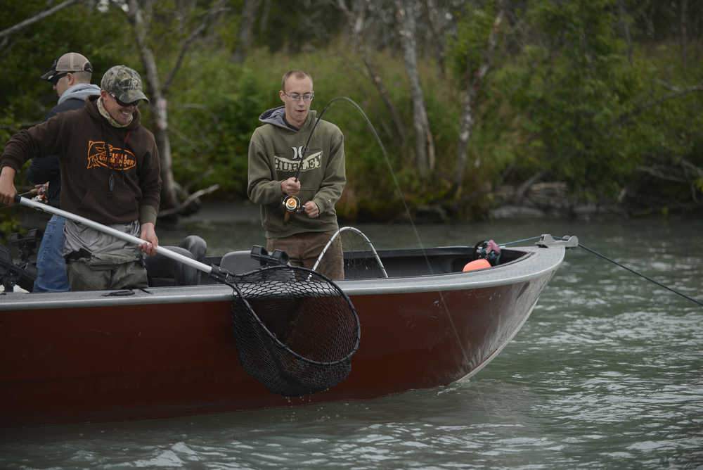 """A guide waits to net a pink salmon caught by a member of military who spent two days fishing on the Kenai River Friday August 8, 2014 near Soldotna, Alaska. The Kenai River Foundation hosted the """"Wounded Heroes"""" fishing event that brought more than 70 military members down to the Kenai River and paired them up with area guides who took them fishing August 8-9. Photo by Rashah McChesney/Peninsula Clarion"""