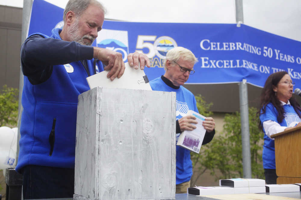 Photo by Kelly Sullivan/ Peninsula Clarion Kenai Peninsula College Direct Gary Turner places an item inside the mock-version of the 50th anniversary time capsul, which will eventually go inside the wall at KPC, during the Kenai Peninsula Borough, Kenai Peninsula College and Kenai Peninsula Borough School District joint 50th anniversary community barbecue, Thursday, August 14, at the KPC Kenai River Campus in Soldotna, Alaska.