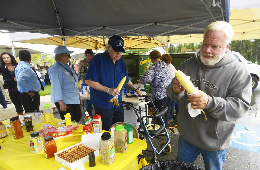 Photo by Kelly Sullivan/ Peninsula Clarion Community member Andy Paule prepares a corn husk during the Kenai Peninsula Borough, Kenai Peninsula College alumni and Kenai Peninsula Borough School District joint 50th anniversary community barbecue, Thursday, August 14, at the KPC Kenai River Campus in Soldotna, Alaska.