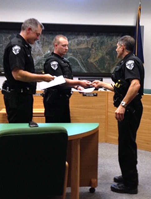 Photo courtesy Shellie Saner, Soldotna city clerk Soldotna Police Chief Peter Mlynarik presents medals to Officers Derek Urban and Stephen Clary for saving a man's life at the Aug. 13 Soldotna City Council meeting. Mlynarik thanked the officers for their actions in rescuing the man from the Kenai River on June 24.