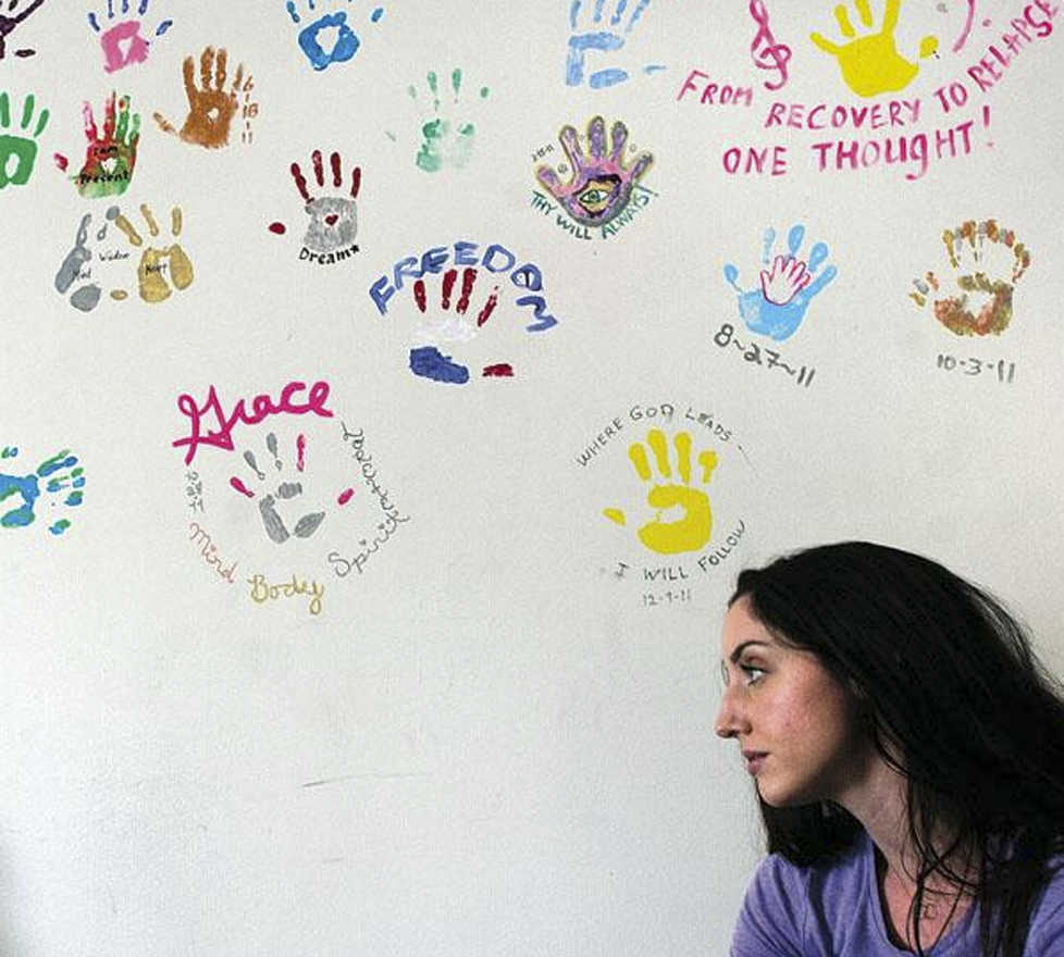 Clarion file photo Kelsey Cusack, volunteer Yoga teacher at the Serenity House treatment center, stands near a wall of handprints made by previous graduates of the substance abuse program. The organization is screening a documentary about addiction on Sunday at the Orca Theater in Soldotna.