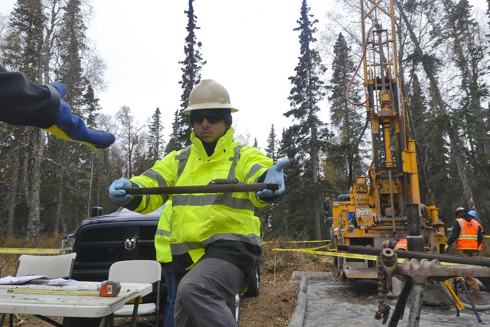 Photo by Rashah McChesney/Peninsula Clarion  Luis Ferreira, geotechnical engineer, passes a soil sample to a representative of the Alaska LNG project from a site near Autumn Street in Nikiski Thursday Oct. 9, 2014 in Nikiski, Alaska. Alaska LNG is conducting geotechnical surveys in an area where they plan to put an LNG facility.