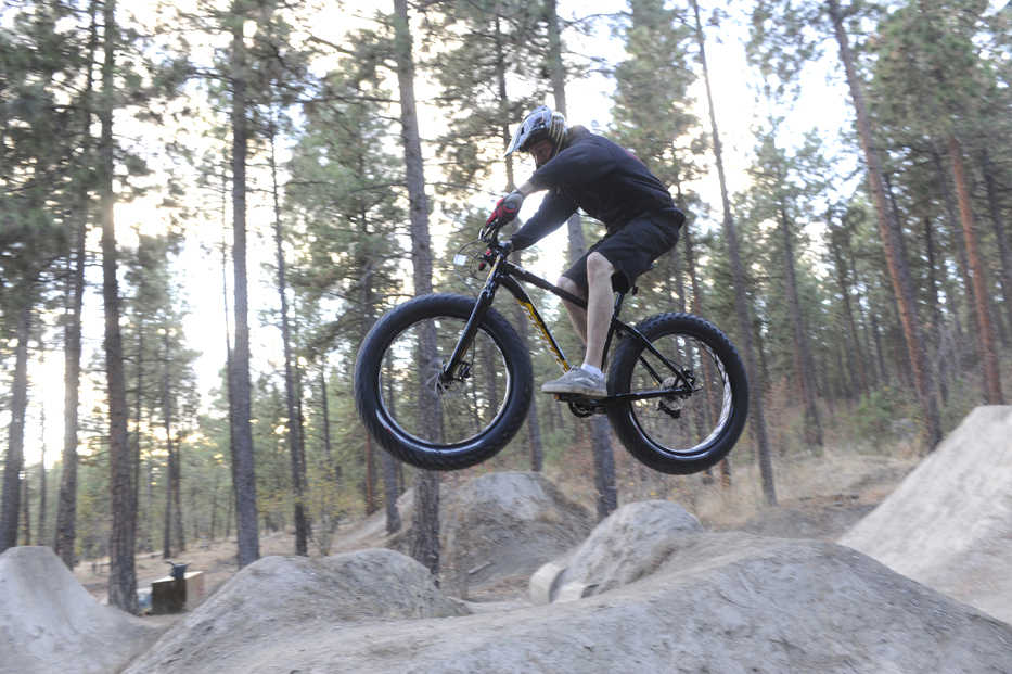 In this Oct. 21, 2014 photo, Ruk Kuchenbecker takes some jumps at the Beacon Hill jumps at Camp Sekani, in Spokane, Wash. The fat bike - a seemingly typical mountain bike frame with tires ranging from 3.7 to 4.8 inches wide - owes its origin to Fairbanks, Alaska. (AP Photo/The Spokesman-Review, Jesse Tinsley)