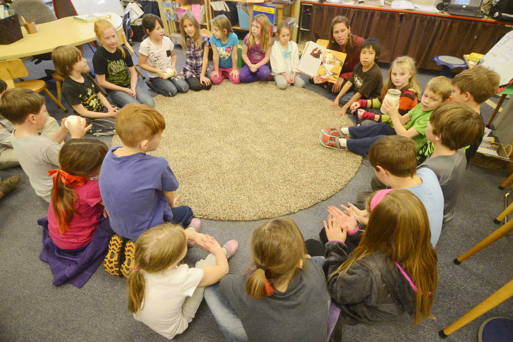 "Photo by Kelly Sullivan/ Peninsula Clarion Students in primary grade teacher Jennifer Hubbard's class listen to a modern version of the folktale ""Stone Soup,"" which the school traditionally cooks ever year before Thanksgiving Tuesday, November 25, 2014, at Soldotna Montessori in Soldotna, Alaska."