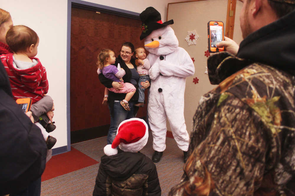Photo by Kelly Sullivan/ Peninsula Clarion Avah, Kenzy and Alyssa Weeks pose for photos with Frosty the Snowman at  Christmas Comes to Kenai November 28, 2014, in at the Kenai Chamber of Commerce and Visitor Center in Kenai, Alaska. Ivan Weeks said it was the first year Avah Weeks would be seeing Santa Claus, but her sister Kenzey Weeks had before.