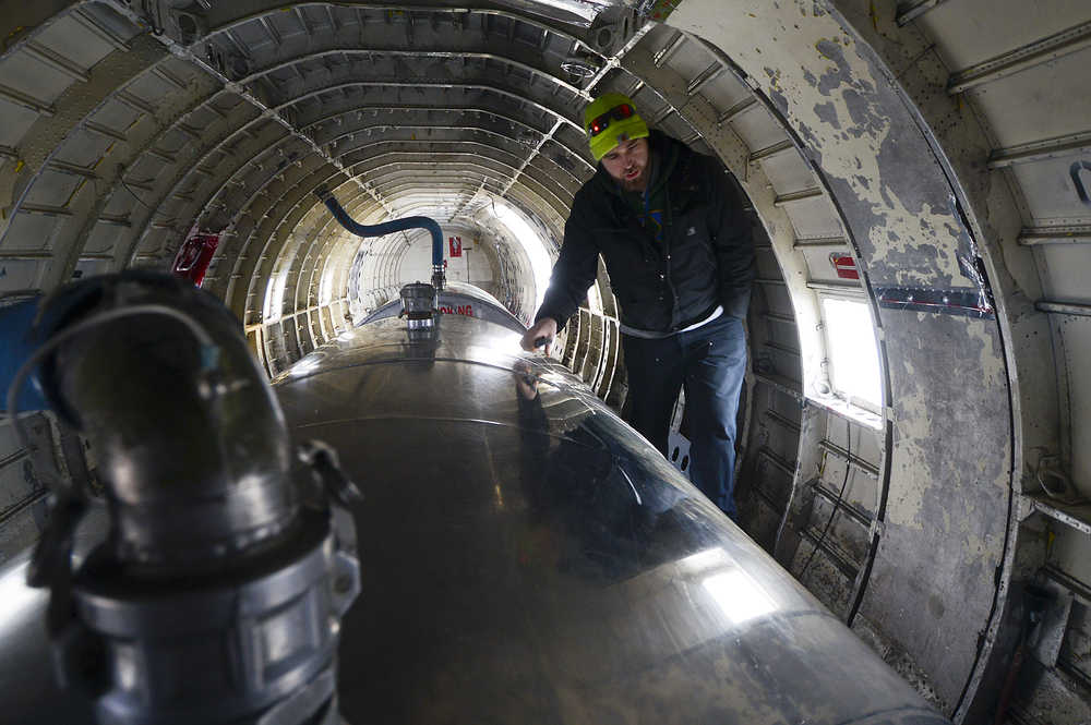 Photo by Rashah McChesney/Peninsula Clarion First Officer Zachary Sawyer walks through the belly of a WWII-era plane used by Everts Air Fuel Service after the plane landed at the Kenai airport to refill its tanks on Tuesday Jan. 13, 2014 in Kenai, Alaska.