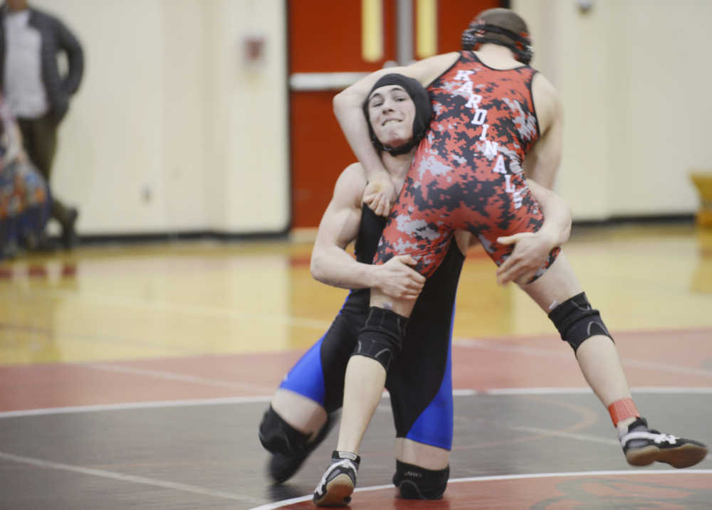 Photo by Kelly Sullivan/ Peninsula Clarion Soldotna High School Star James Gallagher tries to knock Kenai Central High School Kardinal Dylan Carter off his feet during the 182 weight-class match, Thursday, Jan. 22, 2015, at Kenai Central High School in Kenai, Alaska.