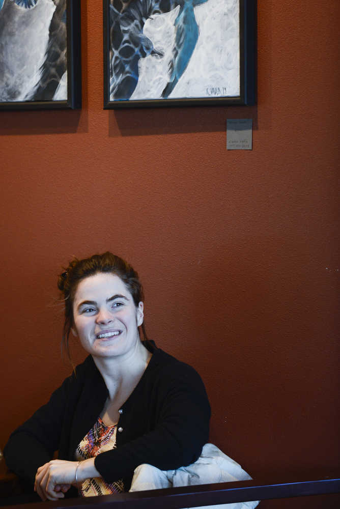 Photo by Rashah McChesney/Peninsula Clarion Kaitlin Vadla looks at her paintings while talking to a reporter on Wednesday Jan. 28, 2015 at The Flats Bistro in Kenai, Alaska.