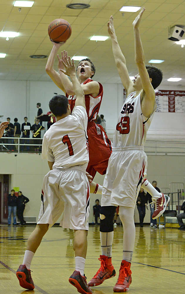 Kenai's Austin McKee floats a shot over Juneau-Douglas defenders Manase Maake (1) and Bruce Jones (43) during the Kardinals' 63-50 loss to the Crimson Bears on Thursday in Juneau.
