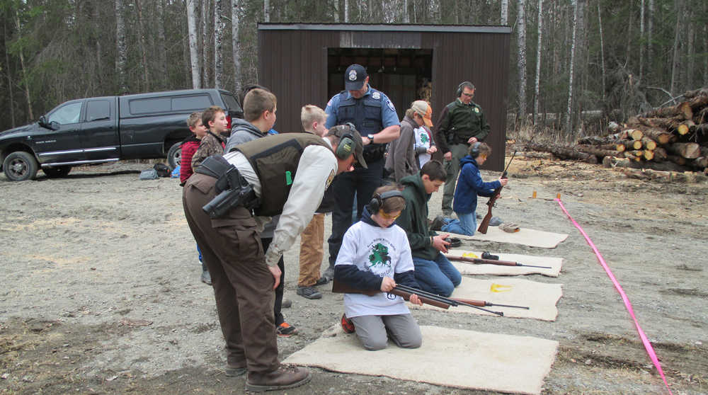 Officers Shay Hurd (Kenai National Wildlife Refuge), Daniel Carnow (NOAA), and Jacques Kosto (Alaska State Parks) help kids learn to shoot with air rifles. (Photo courtesy Kenai National Wildlife Refuge)