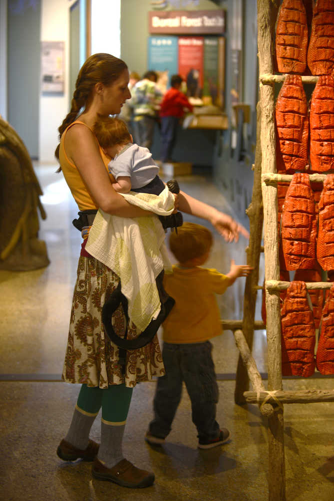 """Ben Boettger/Peninsula Clarion Lacy Ledahl and her children Iver and Ottar examine a model salmon-drying rack at the new Kenai Wildlife Refuge visitor center on Friday, May 3. """"It's beautiful. Much nicer than the one we had when I was a kid,"""" Ledahl said of the new visitor center. """"I told (Iver) he could push all the buttons--that's why we were here so long."""""""
