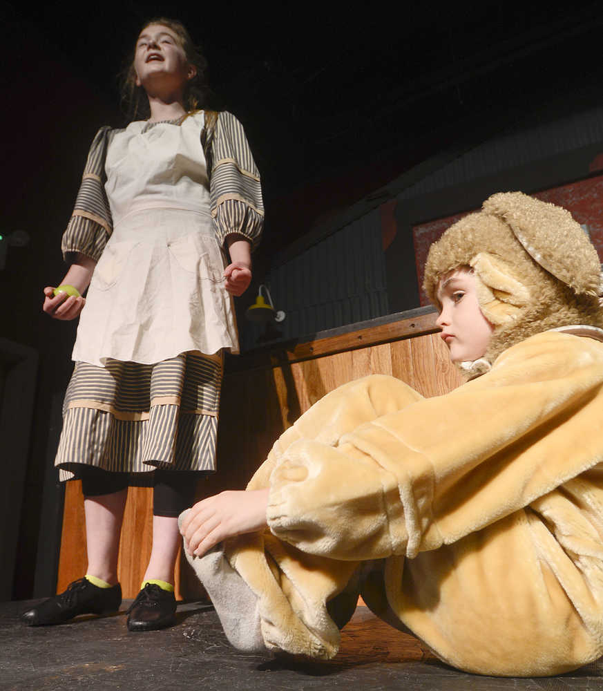 Photo by Rashah McChesney/Peninsula Clarion  Annie (Anya Hondel) and a stray dog Sandy (Kincaid Jenness) rehearse for the Triumvirate Theatre's production of the musical Annie on Tuesday Jan. 13, 2014 in Nikiski, Alaska.