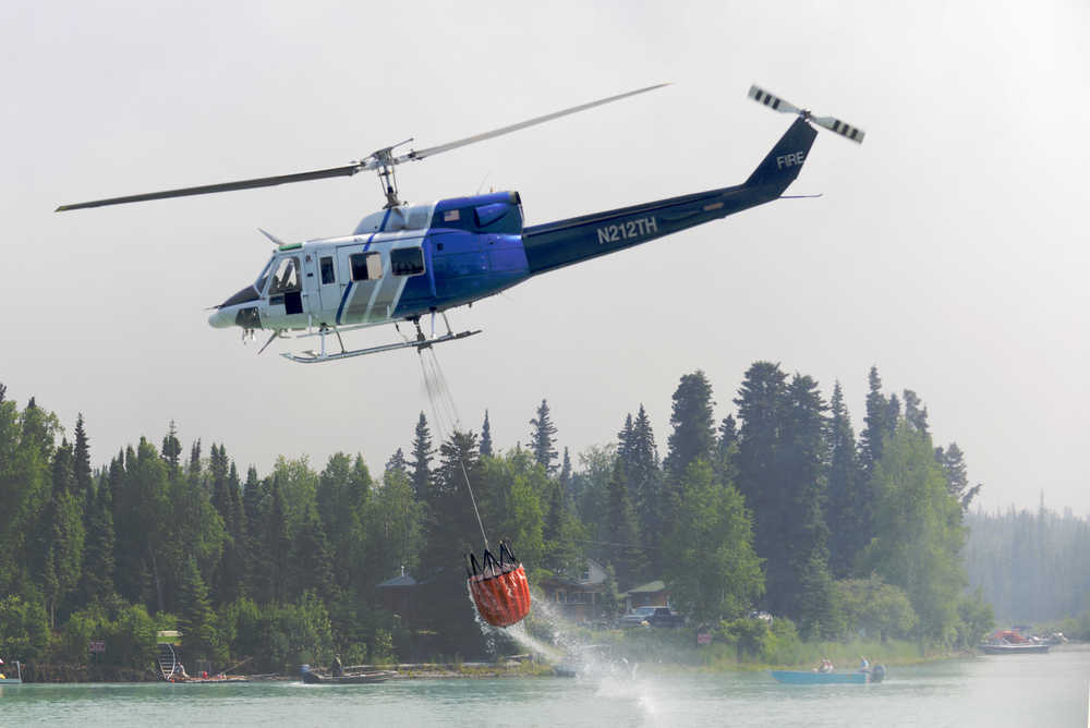 Ben Boettger/Peninsula Clarion A helicopter returns from a dumping run on the north shore of the Kenai River on Tuesday, June 16.