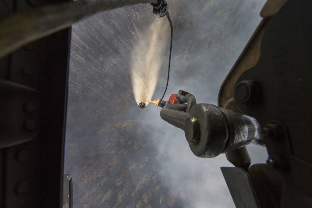 """A """"Bambi Bucket,"""" hanging from an Alaska Army National Guard Black Hawk helicopter, releases more than 700 gallons of water onto the Stetson Creek Fire near Cooper Landing, Alaska, June 17. Two AKARNG Black Hawk helicopters flew 200 bucket missions total, dumping more than 144,000 gallons of water on the 300-acre Stetson Creek Fire on the Kenai Peninsula portion of the Chugach National Forest. (U.S. Army National Guard photo by Sgt. Balinda O'Neal)"""