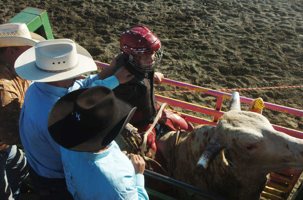 """Photo by Megan Pacer/Peninsula Clarion Several barrel racers warm up before, """"Beauty and the Beast,"""" a combined barrel racing and bull riding competition on Friday night during the Progress Days Rodeo at the Soldotna Rodeo Grounds."""