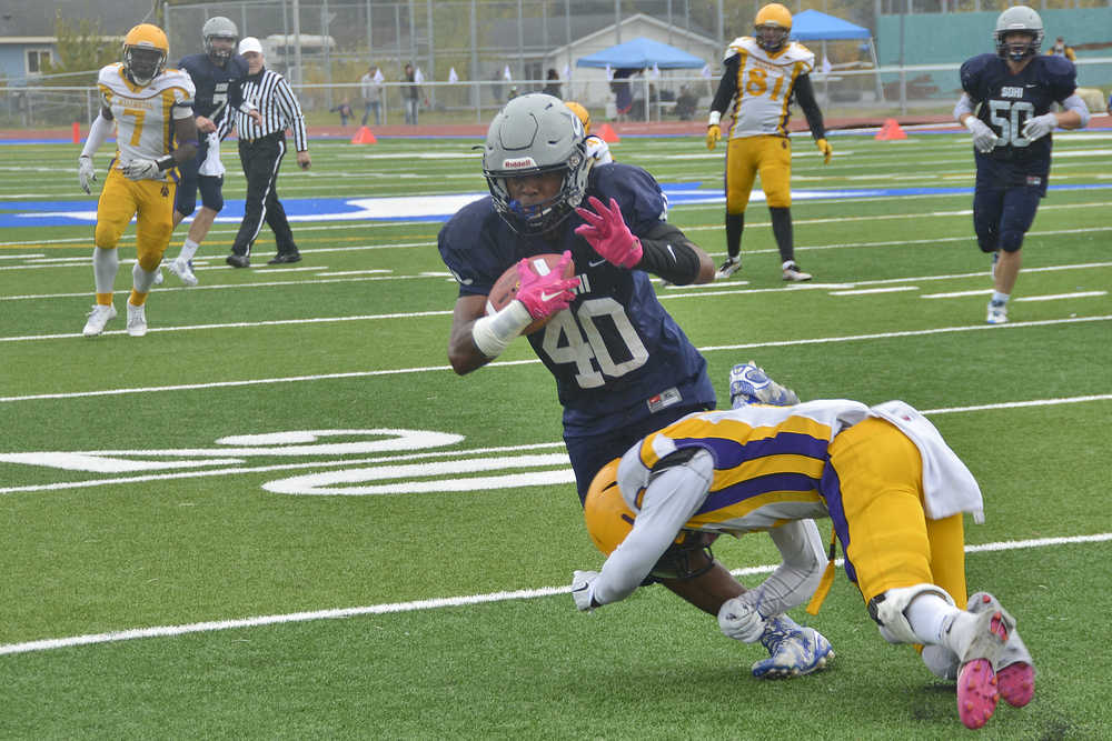 Photo by Rashah McChesney/Peninsula Clarion Soldotna High School's Keola Finau gets tackled by Lathrop's Garrius Maiden during their game on Saturday September 26, 2015 in Soldotna, Alaska.