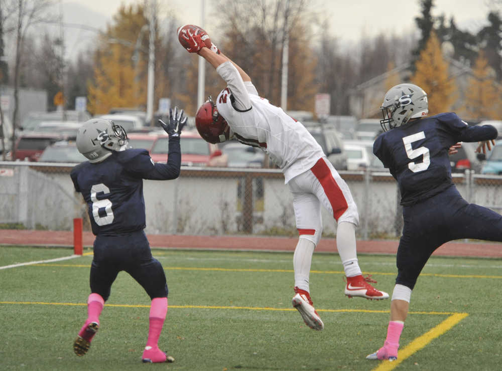 Kenai's Zack Tutle catches a touchdown pass between Soldotna's Dylan Simons, 5 and Jesse Littrel.  Photo for the Clarion by Michael Dinneen