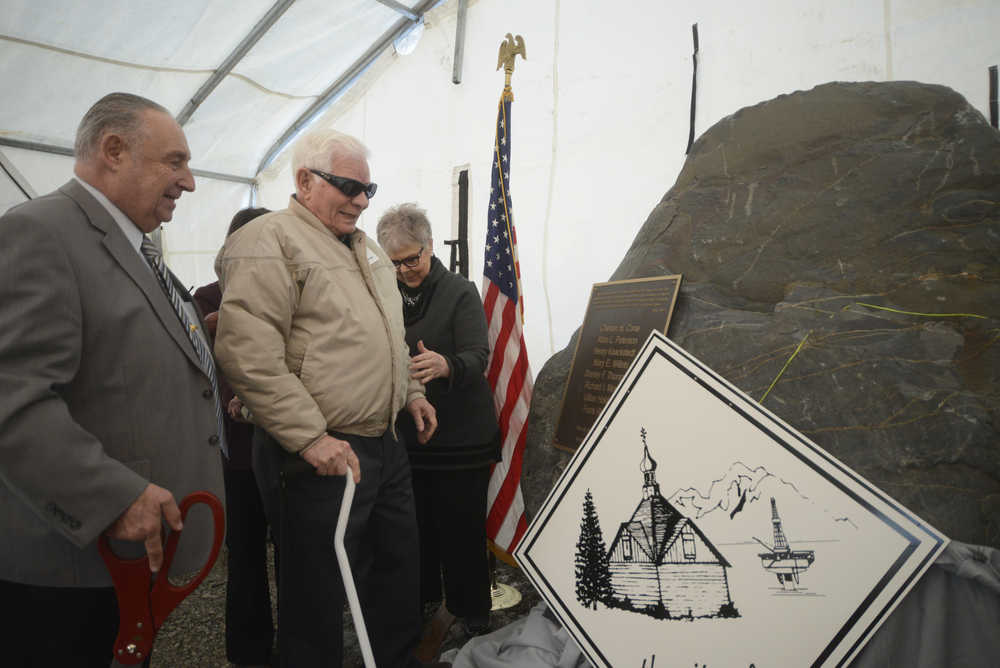 Photo by Megan Pacer/Peninsula Clarion From left to right: former Kenai Mayor John Williams, Kenai Charter Commission member Richard Morgan and Kenai Mayor Pat Porter present a rock affixed with a memorial plaque on Sunday, Nov. 29, 2015 outside City Hall in Kenai, Alaska. The rock was dedicated to honor the commission members who signed Kenai's charter in 1963.
