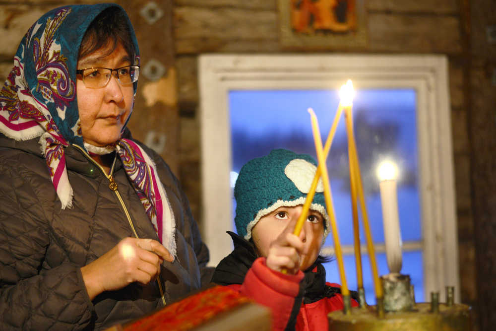 Ben Boettger/Peninsula Clarion Matrushka Lena Nick (left) watches her daughter Ana Nick light a candle before a Divine Liturgy service on Saturday, Dec. 19 at the St. Nicholas Russian Orthodox Chapel  in Kenai. The two came for the service from Ninilchik with Lena's husband, Father Victor Nick of the Holy Transfiguration of Our Lord Chapel.