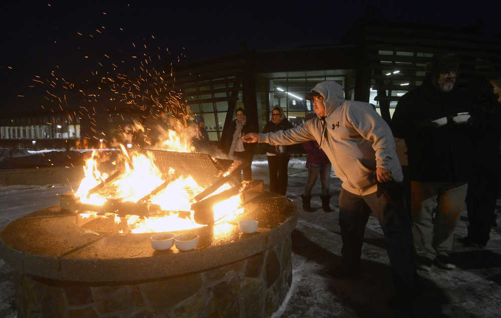 """Photo by Megan Pacer/Peninsula Clarion Soldotna resident Abraham Anasogak throws a plant offering into the flames of a Raven Fire Circle during a healing gathering called """"You and Me"""" on Wednesday, Jan. 20, 2016 at the Dena'ina Wellness Center in Kenai, Alaska. The gatherings are held periodically to support those affected by suicide or death, and have lavender, sage and sweetgrass available for participants to burn in the healing process."""