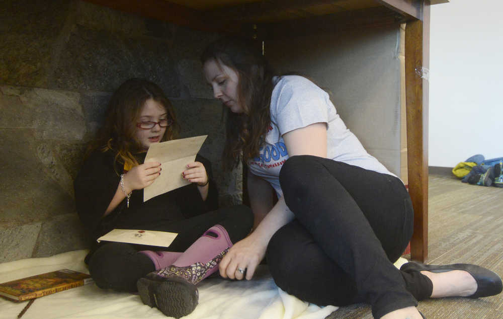 """Photo by Megan Pacer/Peninsula Clarion Mariah Ross and her 6-year-old daughter, Adelynn, read tucked away in a makeshift """"cupboard under the stairs"""" during Harry Potter Book Night on Thursday, Feb. 4, 2016 at the Soldotna Public Library in Soldotna, Alaska."""