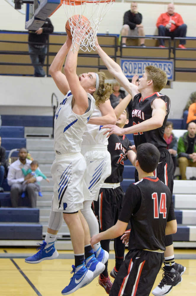 Photo by Joey Klecka/Peninsula Clarion Palmer senior forward Michael Kluting attempts a layup amid a scrum of Kenai Central players, including sophomore Garrett Fitt (right) and senior Marshall Vest (bottom), Saturday at Palmer High School. The Moose defeated the Kardinals 46-33.