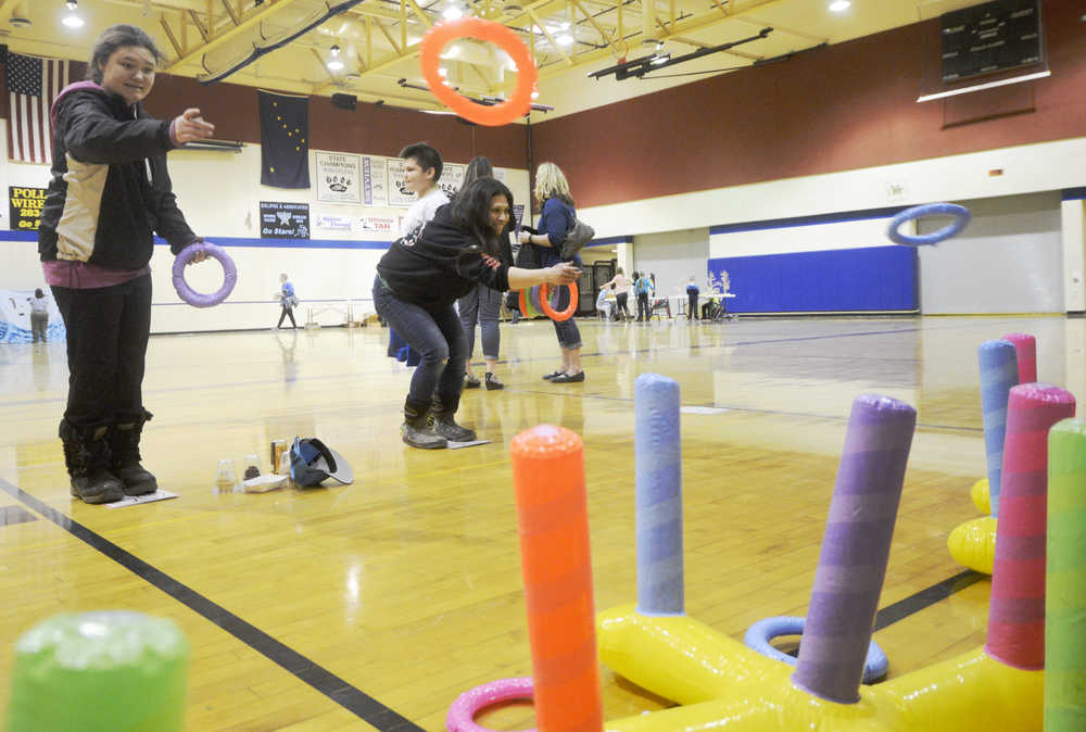 Jordan Tackett (left) plays a ring-toss game against her mother during the Autism Extravaganza awareness fair at Soldotna Preparatory School on Saturday, April 4. Tackett, who is autistic, was among those who came to play games and socialize during the event.