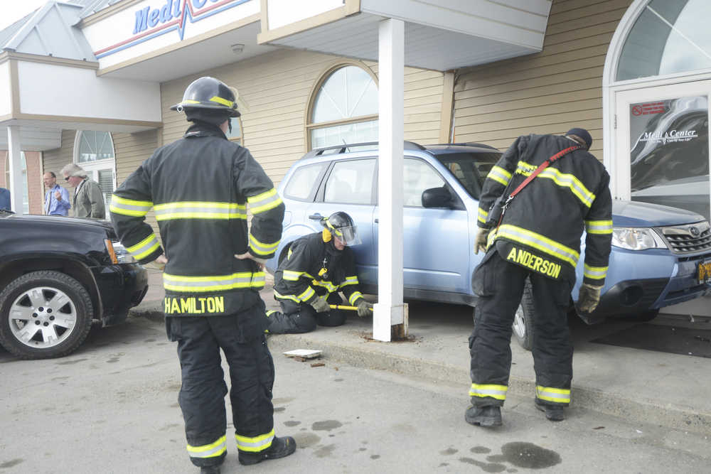 Photo by Megan Pacer/Peninsula Clarion Members of the Kenai Fire Department knock pillars back into place after a driver backed onto the pavement and struck the MediCenter building on Monday, April 11, 2016 in Kenai, Alaska.