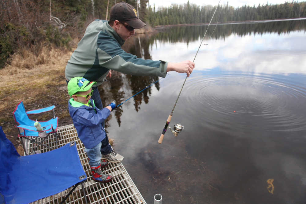 """Photo by Kelly Sullivan/ Peninsula Clarion (Not pictured) Aimee, (left) Rudy and Sam Zulkanycz get in some early spring fishing Monday, April 18, 2016, at Loon Lake in Soldotna, Alaska. Sam said the quiet spot is a family favorite, especially when the sun is out and there is no one else on the joining them on the perimeter. """"They aren't the biggest and best fish by that's okay,"""" he said."""