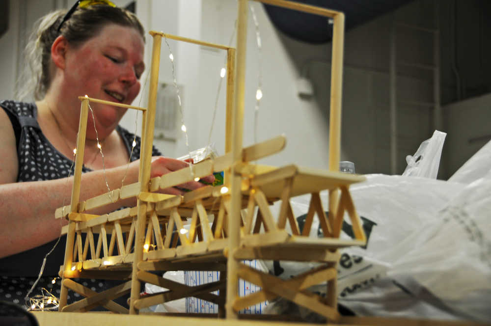 Photo by Elizabeth Earl/Peninsula Clarion Holly West, a senior at Kenai Peninsula College, works on her project at the college's 3D design studio on Friday, April 15, 2016. West said her project, building the Bay Bridge from popsicle sticks, is part of a project conveying the connection her uncle had traveling back and forth from China for work.