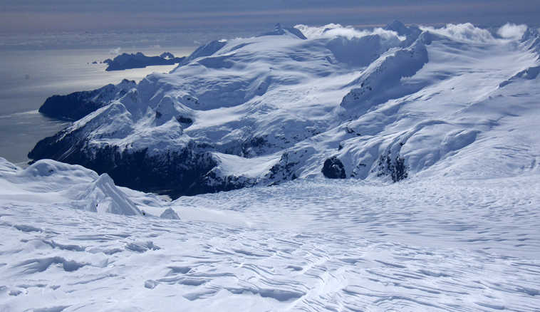 This Friday, April 8, 2016, photo provided by Jenny Neyman shows the view from the Harding Ice Field south of Seward on the Kenai Peninsula at about 5,000 feet elevation, overlooking Aialik Glacier, in Kenai Fjords National Park, Alaska. Two skiers stranded for four nights on the Alaska ice field braved cold and hunger but also claustrophobia as the ceiling of snow cave they dug for shelter sagged close to their faces. Chris Hanna and Jenny Neyman say they thought the cave Hanna tunneled under 4 feet of snow might collapse before rescuers could reach them. (Jenny Neyman via AP)