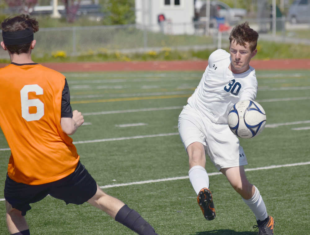 Photo by Joey Klecka/Peninsula Clarion Soldotna sweeper Ethan Bott (30) keeps the ball away from West Anchorage's Cannen Burgess at the ASAA state soccer tournament Thursday at Eagle River High School.