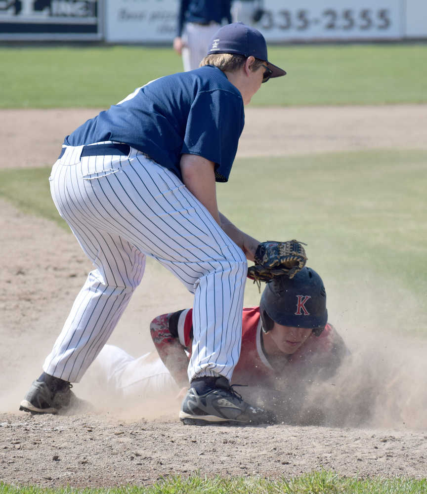 Photo by Jeff Helminiak/Peninsula Clarion Kenai Central's Paul Steffensen slides under the tag of Soldotna third baseman Jake Marcuson for a stolen base Saturday in the second-place game of the Southcentral Conference tournament at Coral Seymour Memorial Park in Kenai.