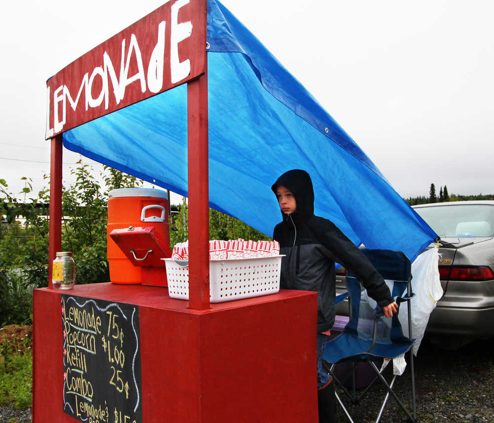 Paxton McKnight sets up his lemonade and popcorn stand near the Sushi Exchange restaurant on Saturday, June 11 in Soldotna. McKnight was one of several local children who participated in Lemonade Day, an event created by the Kenai Chamber of Commerce to promote business skills among youth.