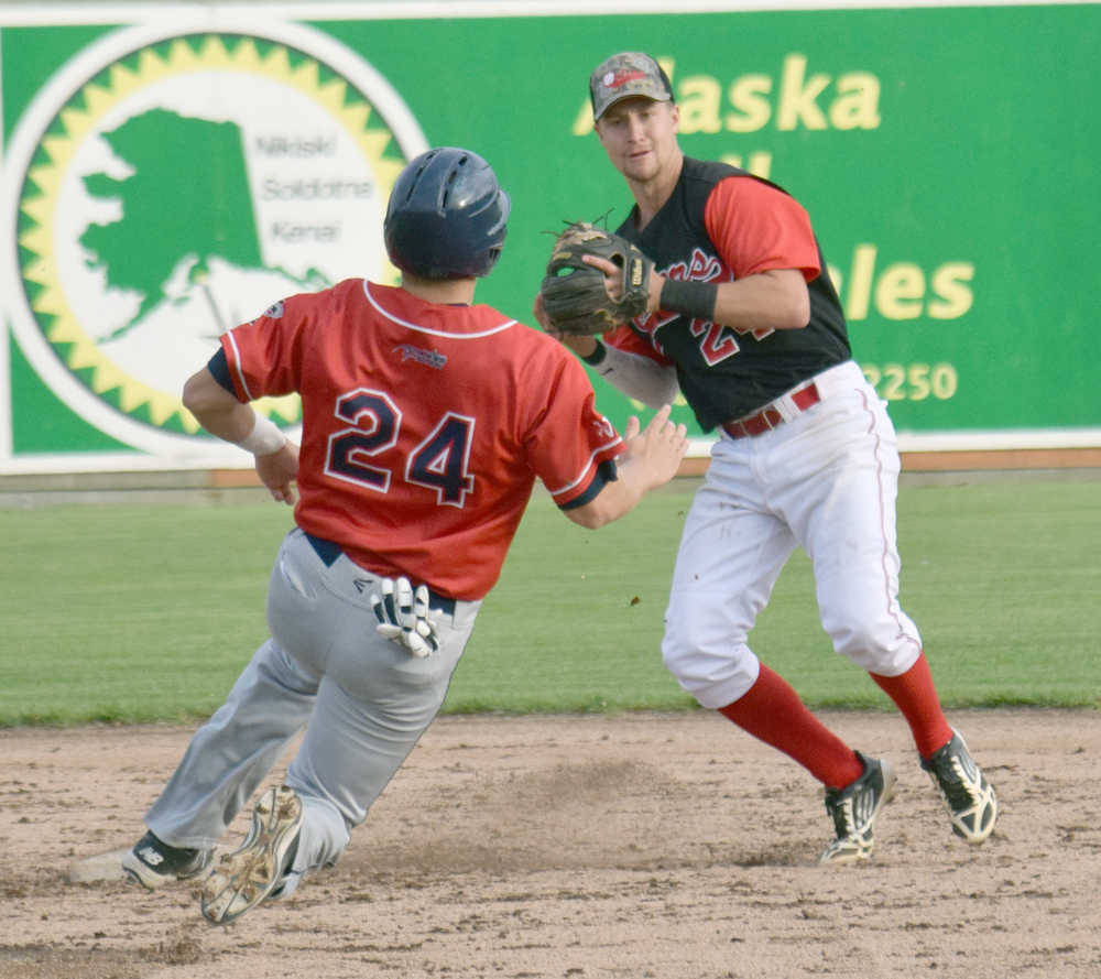 Photo by Jeff Helminiak/Peninsula Clarion Oilers shortstop Trey Dawson helps get his team out of a jam by turning a double play in front of Chinooks third baseman Tim Millard in the eighth inning Friday at Coral Seymour Memorial Park in Kenai.