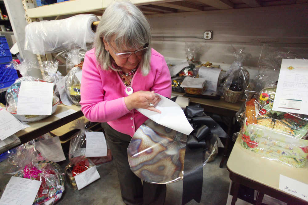 Photo by Kelly Sullivan/ Peninsula Clarion Kenai Peninsula Food Bank Executive Director Linda Swarner searches through this year's donations for the  20th annual Soup Supper on Monday, Aug. 15, 2016 at the Kenai Peninsula Food Bank in Soldotna, Alaska.