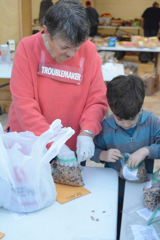 Kaye Fariday helps a boy /name??// from Fireweed Academy bag food at the Homer Food Pantry on Sept. 26 at Homer United Methodist Church.