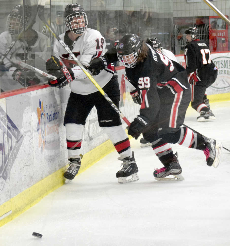 Photo by Jeff Helminiak/Peninsula Clarion Kenai Central's Matthew Zorbas and Houston's Ree Humphreys tangle along the boards Friday at the Soldotna Regional Sports Complex during the Peninsula Ice Challenge.