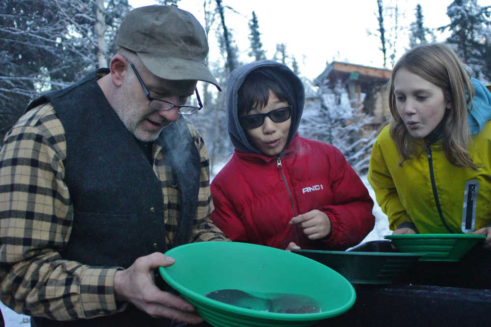 Ben Boettger/Peninsula Clarion Prospector Steve Morris (left) taps a pan of water and concentrated sediment, which he dredged from a nearby river, to reveal gold flakes to onlooking Seward Elementary students Bengimiin Ambrosiani and Aloshia Cross during a fieldtrip to Manitoba Cabin on Tuesday, Nov. 15, near the Seward Highway.