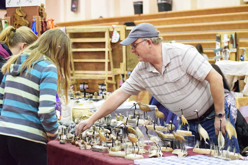 Photo by Megan Pacer/Peninsula Clarion Bill Matthews shows the wares  of Two Spirits Gallery in Wasilla to passing potential customers Friday, Nov. 25, 2016 during the Fine Arts and Craft Fair at Kenai Central High School in Kenai, Alaska. Karen Tocktoo, the gallery's owner, said this is the best fair she travels to.