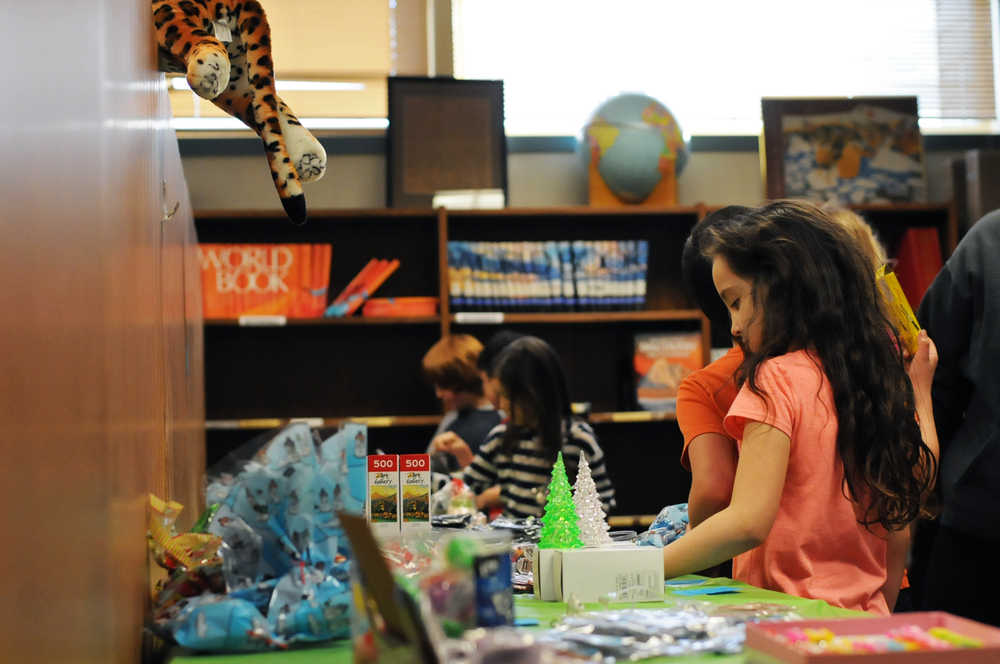 Photo by Elizabeth Earl/Peninsula Clarion A Soldotna Elementary School student peruses the items available in the holiday gift shop put on by the school's Parent-Teacher Organization in the library on Wednesday, Dec. 14, 2016 in Soldotna, Alaska.