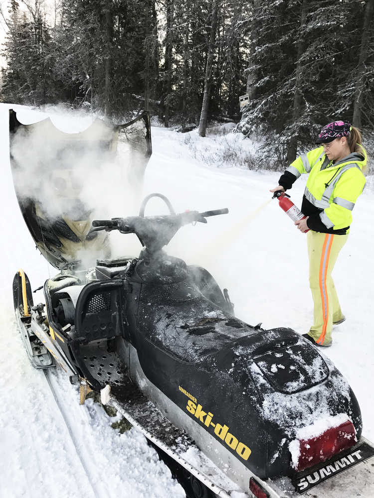 Photo courtesy Laurie Speakman This photos taken Tuesday, Jan. 3, 2017 on Kalifornsky Beach Road between Kenai and Soldotna shows Laurie Speakman, a volunteer driver for the Alaska Moose Federation on the Kenai Peninsula, putting out a snowmobile fire. She used two fire extinguishers to subdue the flames, one from home and one from her truck used to salvage moose, when she noticed a teen in distress on the side of the road.
