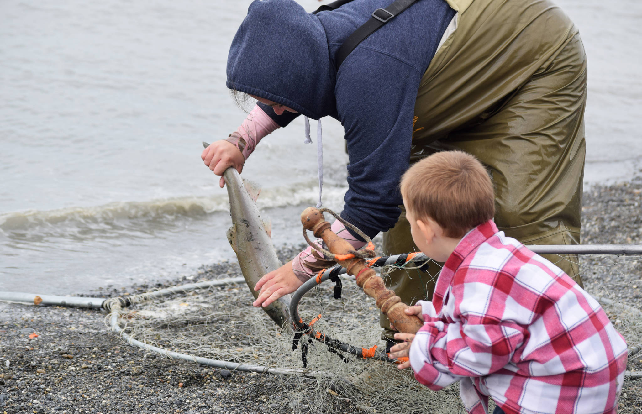 Onya Pate (left) of Soldotna lifts a sockeye salmon she caught in the Kasilof River from her dipnet while her son Epic Lee (right) hands her a bonker on Tuesday, July 31, 2018 in Kasilof, Alaska. (Photo by Elizabeth Earl/Peninsula Clarion)